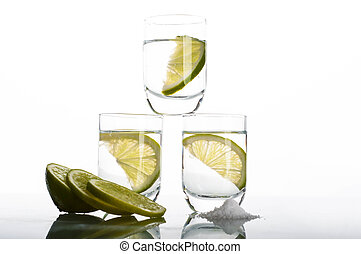 Three shots of vodka with lime
