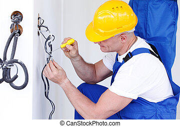 electrician at work - electrician making wiring at new house