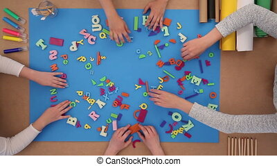 Back to school - children playing with plastic letters
