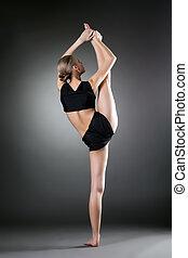 Back view of flexible girl doing vertical split