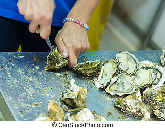Close-up of worker opening oysters - Close-up of worker...