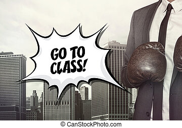 Go to class text with businessman wearing boxing gloves on...