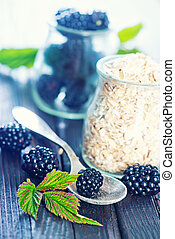 oat flakes with black berries on the wooden table