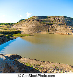 Sand quarry with a pond against blue sky