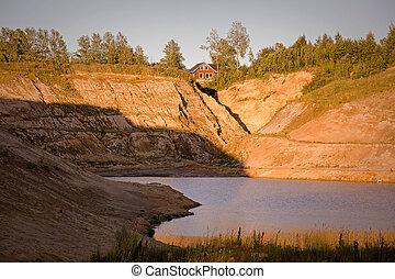 Sand quarry with a pond against blue sky