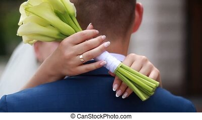 bride embraces groom with flowers in their hands