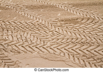 Tire tracks and footprints in sand on a beach