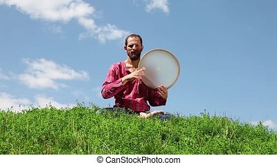 Young man playing the tambourine on - Young man sitting on...