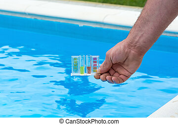 Pool water testing - Tester for pool in a hand against the...
