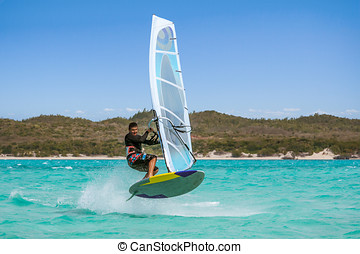 Windsurfer jumping with his sailboard