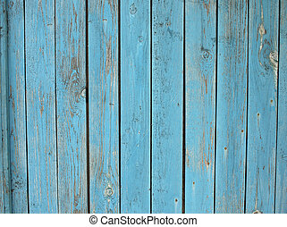 Old wooden planks standing upright with a shabby blue paint...