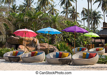 Swimming pool and beach chairs in a tropical garden,...