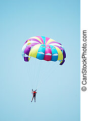 Multi coloured parachute over the blue sky