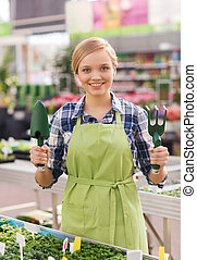 happy woman with gardening tools in greenhouse