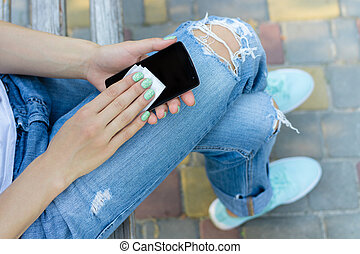Hands of a young girl wipe mobile phone antibacterial cloth....