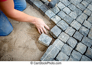 industrial construction worker laying cobblestones and stone blocks on pavement