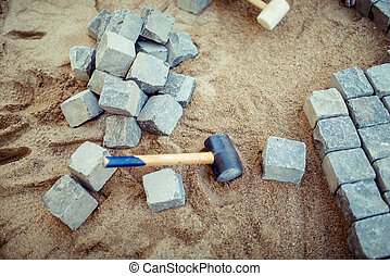 Stone pavement blocks, on sand, with tools and construction details. Laying the pavement cobblestone for outdoor terrace