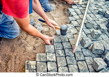 paving pavement with granite stones, workers using industrial cobblestones for paving terrace, road or sidewalk