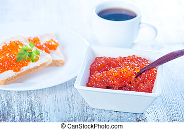 salmon caviar and bread on a table