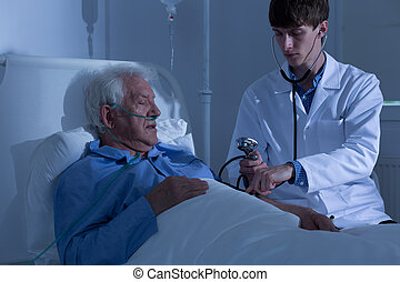 Measuring blood pressure in hospital - Young doctor...