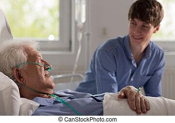 Grandson visiting ill grandfather - Smiling grandson...