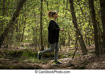 Woman warming up - Running woman warming up in the forest