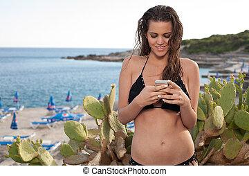 girl in a bikini using smart phone