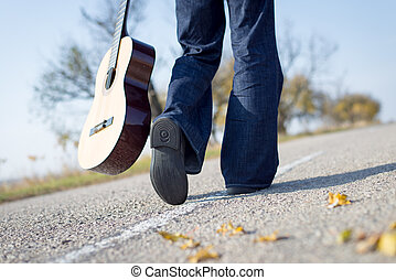 Legs walking away with guitar aside on empty country road -...