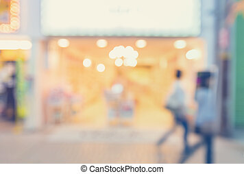 Blurred shopping mall store front with women walking -...