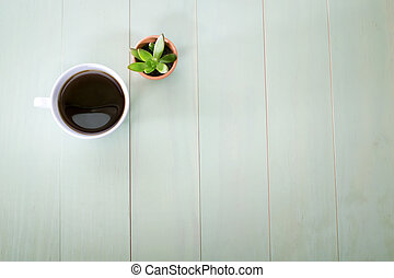 Cup of coffee and small plant in a pot on pastel green...