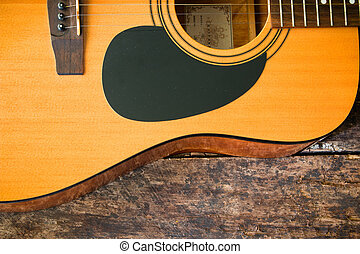half of an acoustic guitar on a wooden background