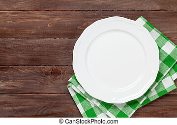 Empty plate over wooden table background View from above...