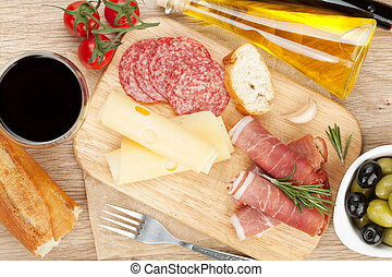 Red wine with cheese, prosciutto, bread, vegetables and...