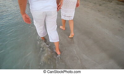 Couple walking on beach. Young happy interracial couple...