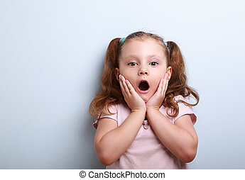 Fun surprising kid girl with opened mouth looking on blue...