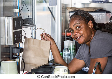 Smiling African-American Worker Hands Food Order Out Window...