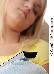 Watching tv - Young blond woman with remote control sleeping...