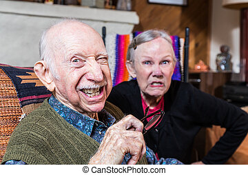 Angry Old Couple - Angry old couple sitting indoors with...