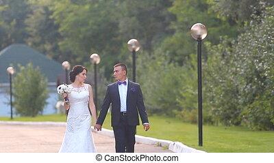 Bride and groom walking away in summer park
