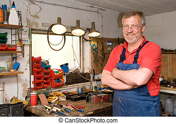 Craftsman - Smiling and happy senior craftsman in his garage