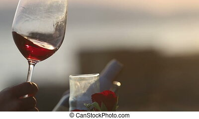 woman and man turn red wine round glass walls at sunset