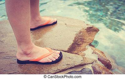 Female legs at swimming pool