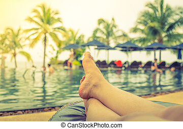 Female legs in the swimming pool water ( Filtered image...