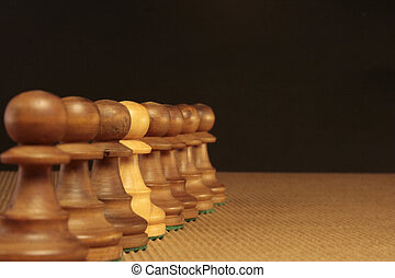 diversity - a white pawn among many black pawns in a...