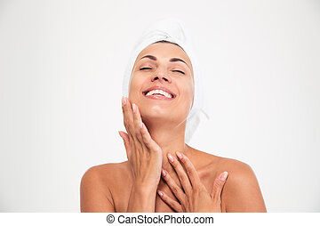 Woman with towel on head touching her fac - Spa concept...