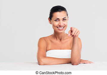 Happy woman in towel pointing finger at camera