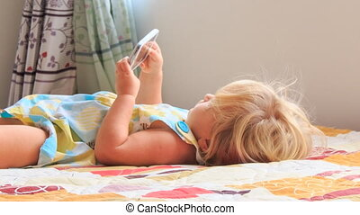 small blonde girl plays with smartphone closeup - little...