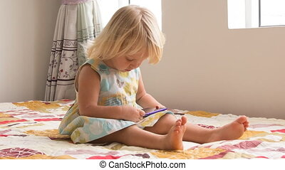 small blonde girl plays with smartphone - small blonde two...