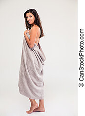Happy woman standing in towel isolated