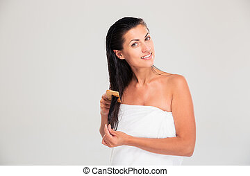 Portrait of a happy woman combing her hair